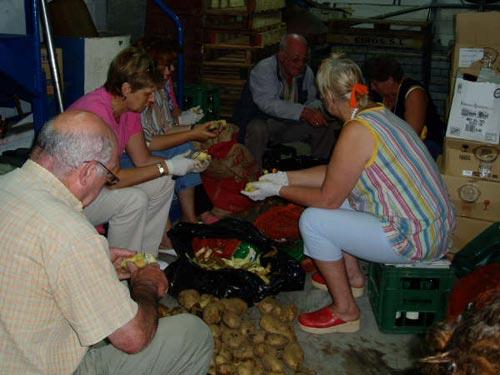 Varias personas preparando las patatas para la marmitada - Se abre en una nueva ventana