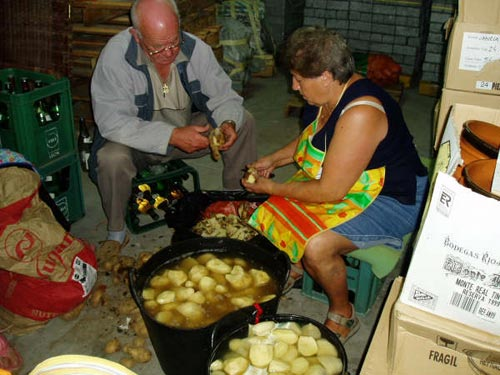 Dos personas se encuentran pelando patatas para la marmitada - Se abre en una nueva ventana