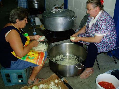 Dos mujeres pelan y cortan cebolla para la marmitada