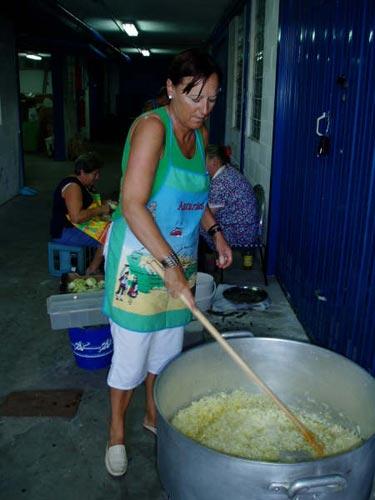 Una mujer revisa y remueve la cebolla para la marmitada - Se abre en una nueva ventana