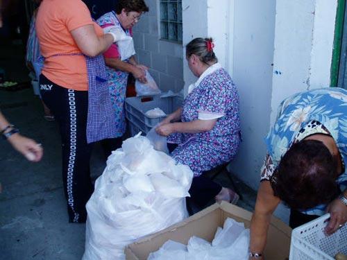 Varias personas preparan las bolsas de la marmitada - Se abre en una nueva ventana