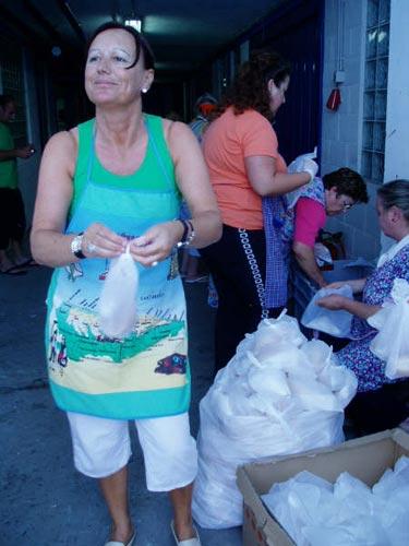 Varias mujeres preparan el pan que se entregará con la marmitada - Se abre en una nueva ventana