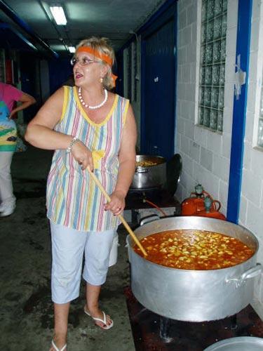 Una mujer revisa y remueve una olla con la marmitada - Se abre en una nueva ventana
