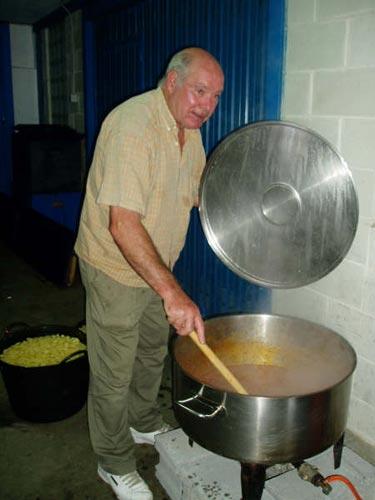 Un hombre revisa y remueve una olla con la marmitada - Se abre en una nueva ventana