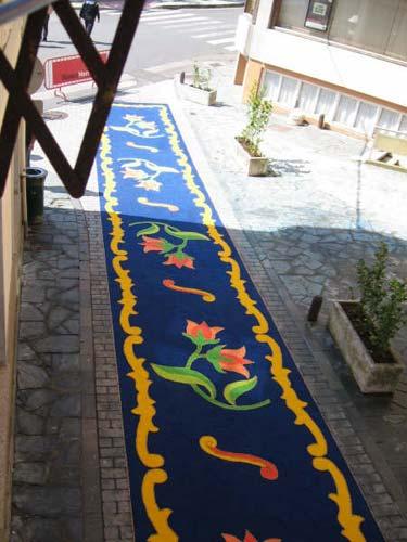 Calle decorada con flores con un fondo azul formando imágenes florales verdes y rojas - Se abre en una nueva ventana