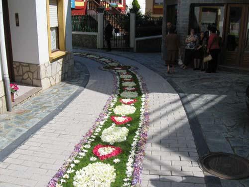 Calle decorada con flores, en un fondo verde se visualizan figuras con flores blancas y rosas - Se abre en una nueva ventana