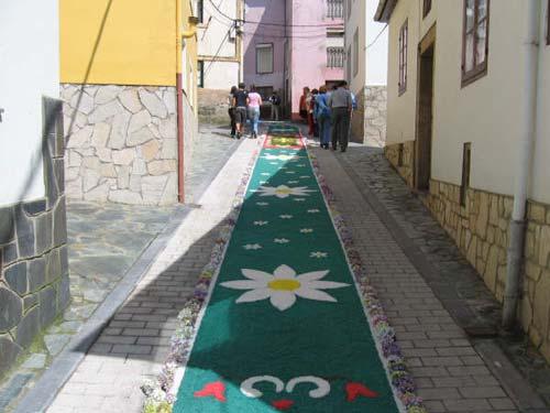 Calle decorada con flores, el fondo es verde y se muestran figuras con forma de margaritas - Se abre en una nueva ventana