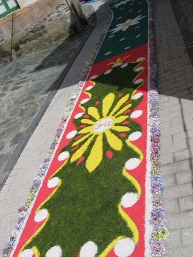 Calle decorada con flores, el fondo es verde en la mayor parte predominando también los colores rojos y blanco, se visualizan algunas figuras de margaritas - Se abre en una nueva ventana