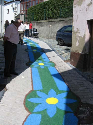 Calle decorada con flores, el fondo de verde en su mayor parte y se muestran margaritas con hojas azules - Se abre en una nueva ventana