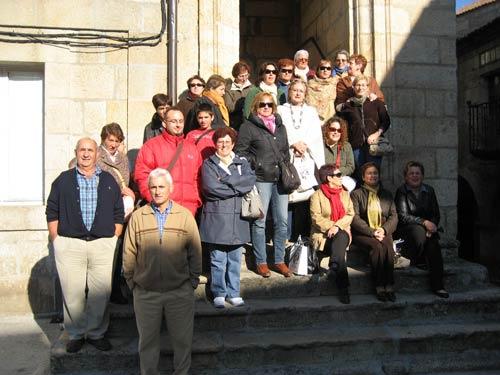 Las personas asistentes a la Excursión a Ribadavia posan junto a un monumento