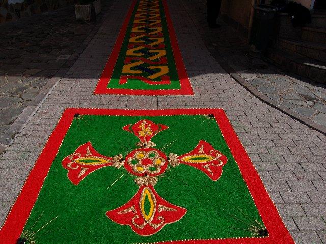 cruz elaborada en sal, arroz y cordón con fondo verde y dibujo en rojo, amarillo y dorado - Se abre en una nueva ventana