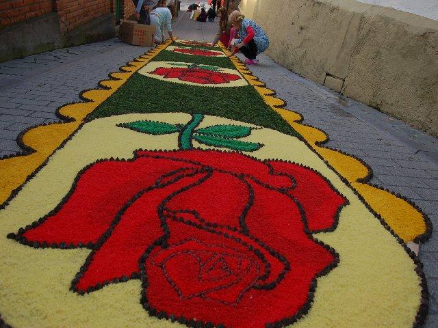 Primer plano del dibujo, una rosa en sal teñida de rojo, verde y fondo amarillo claro con los bordes en eucalipto - Se abre en una nueva ventana