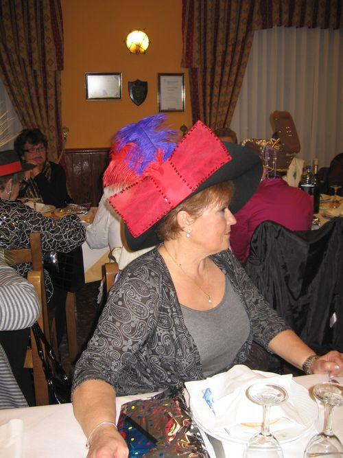 sombrero negro con plumas y un gran lazo rojo - Se abre en una nueva ventana
